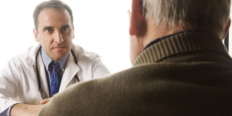 Alter Mann sitzt beim Arzt