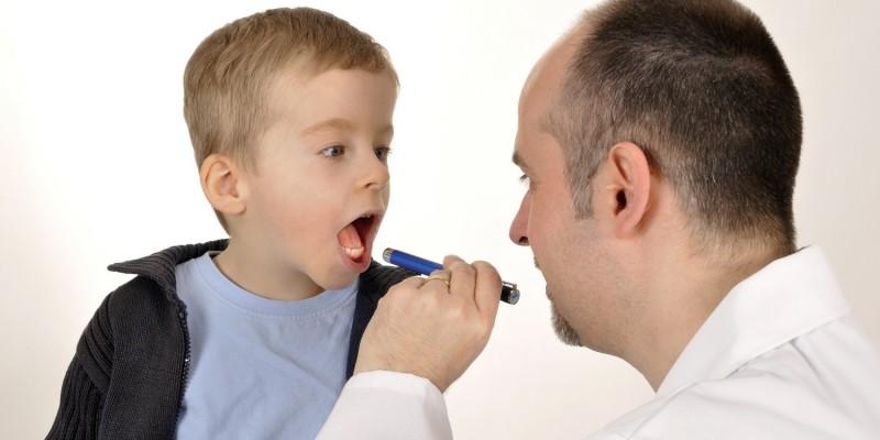 Kinderarzt untersucht den Rachen