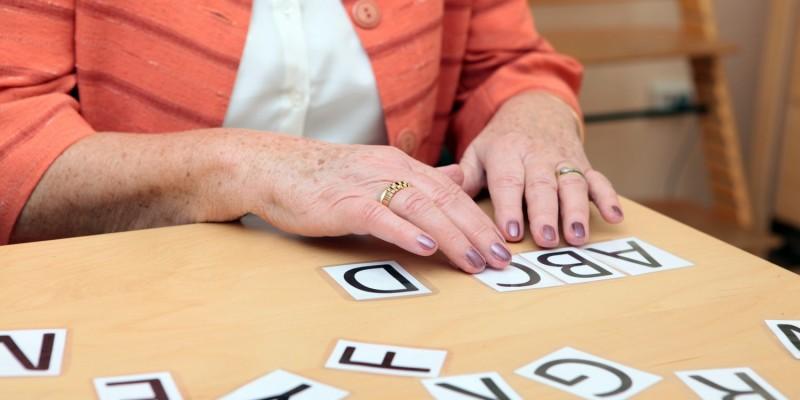 Alte Frau legt Buchstaben in einer Behandlung