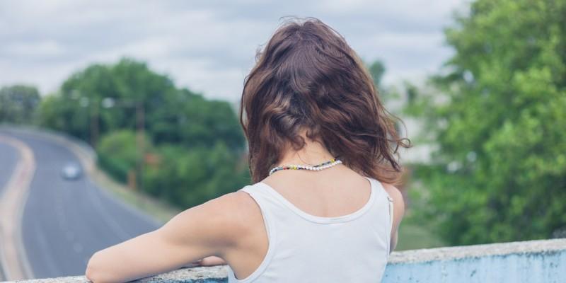 Frau steht auf einer Brücke