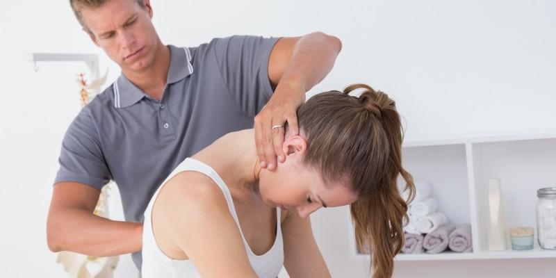 Frau wird mit Verspannungen im Nacken behandelt