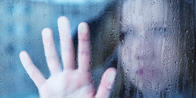 Betrübte Frau am verregneten Fenster