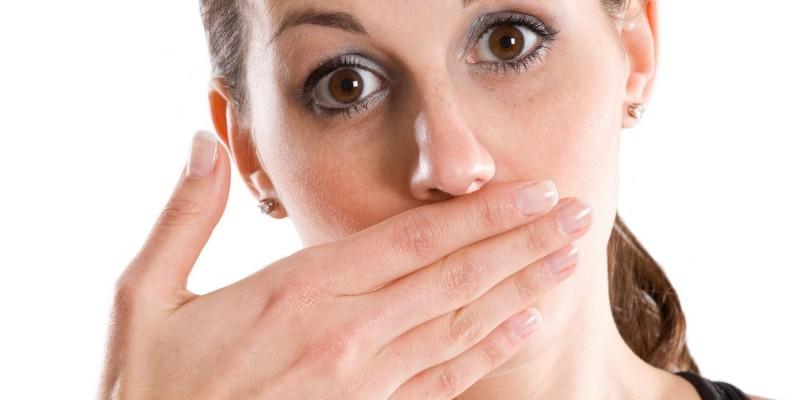 Frau hält sich die Hand vor den Mund
