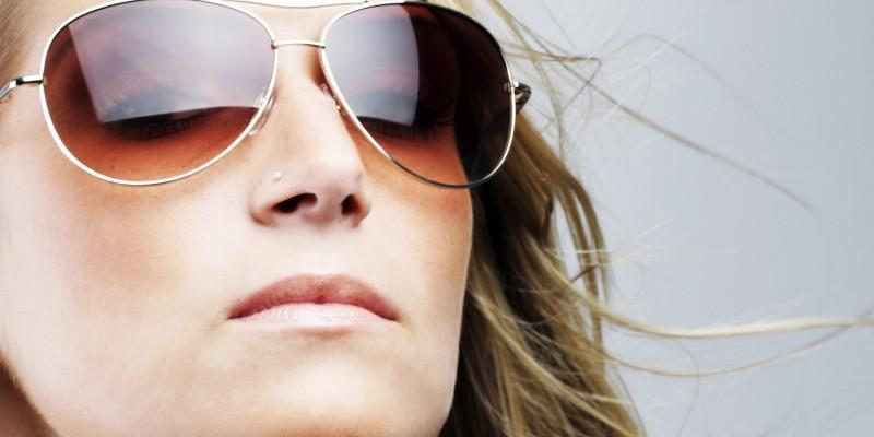 Frau schützt sich mit einer Sonnenbrille vor zu hellem Licht