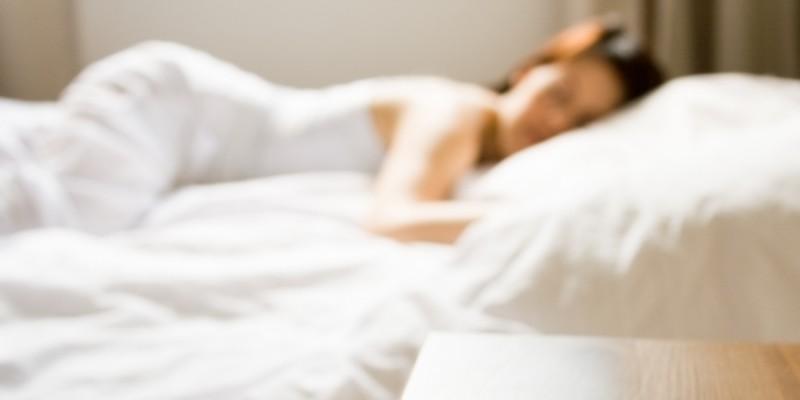 Junge Frau liegt kraftlos im Bett