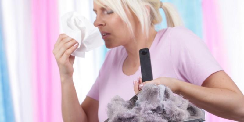 Frau niest beim Hausputz