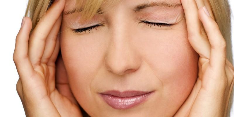 Frau mit schmerzverzerrtem Gesichtsausdruck