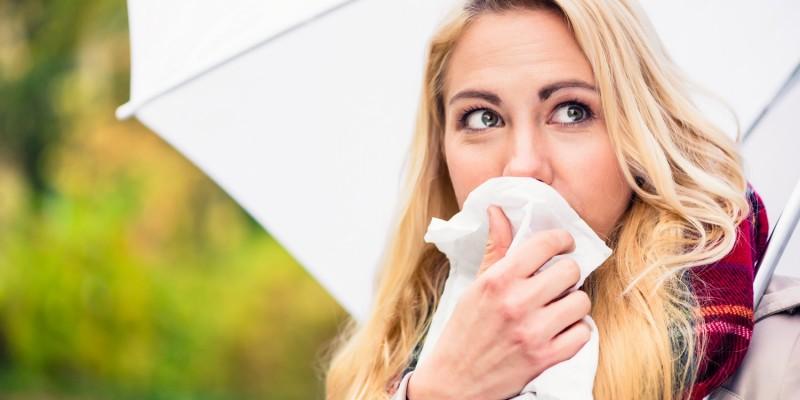 Frau putzt sich die Nase mit einem Taschentuch